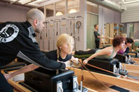 Power Pilates instructor with students